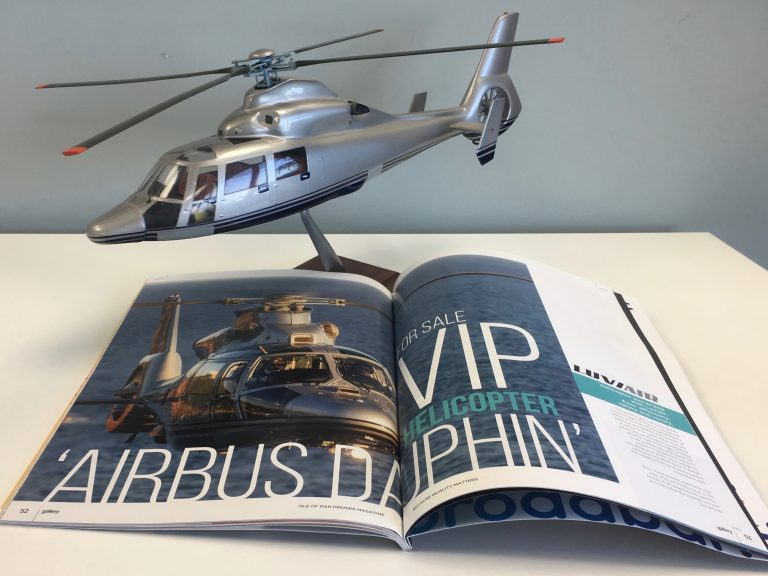 "Small scale model of AS365N3 Helicopter behind an open magazine with helicopter picture on it, showing ""VIP Helicopter: Airbus Dauphin"""