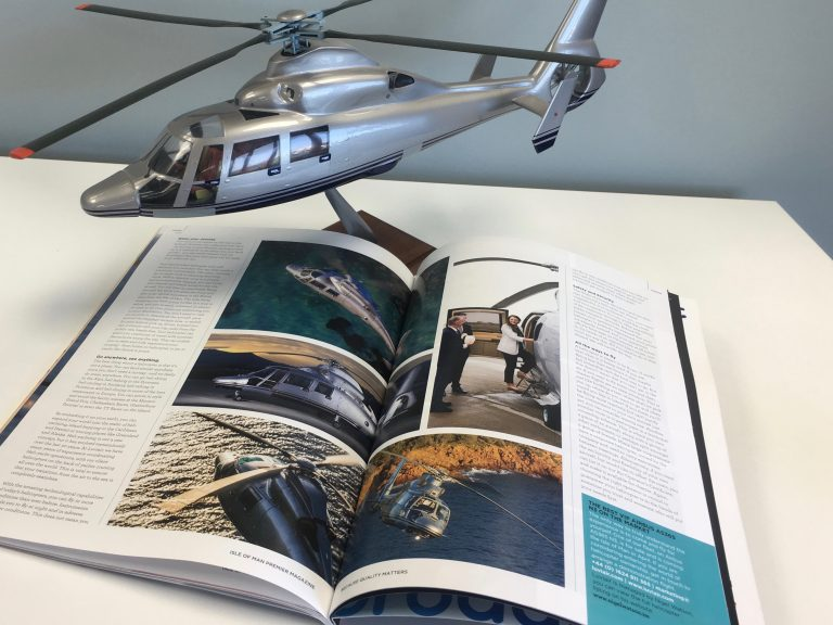 Small scale model of AS365N3 Helicopter behind an open magazine with helicopter pictures on it.