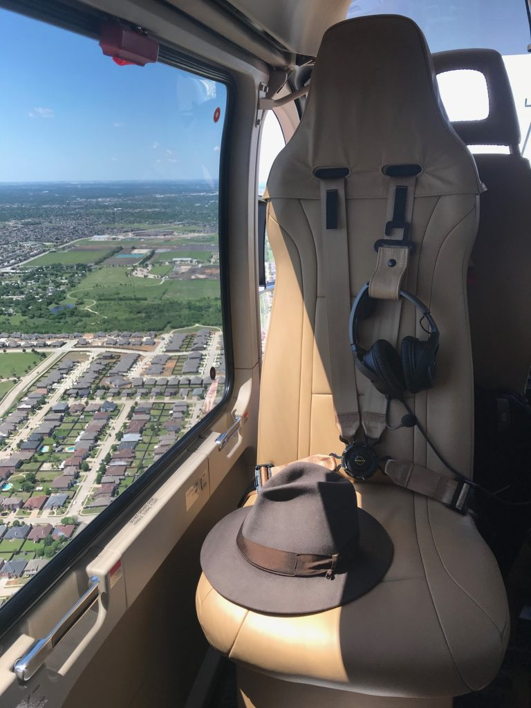 Rear-facing helicopter seat from inside of cabin during flight with hat on it.