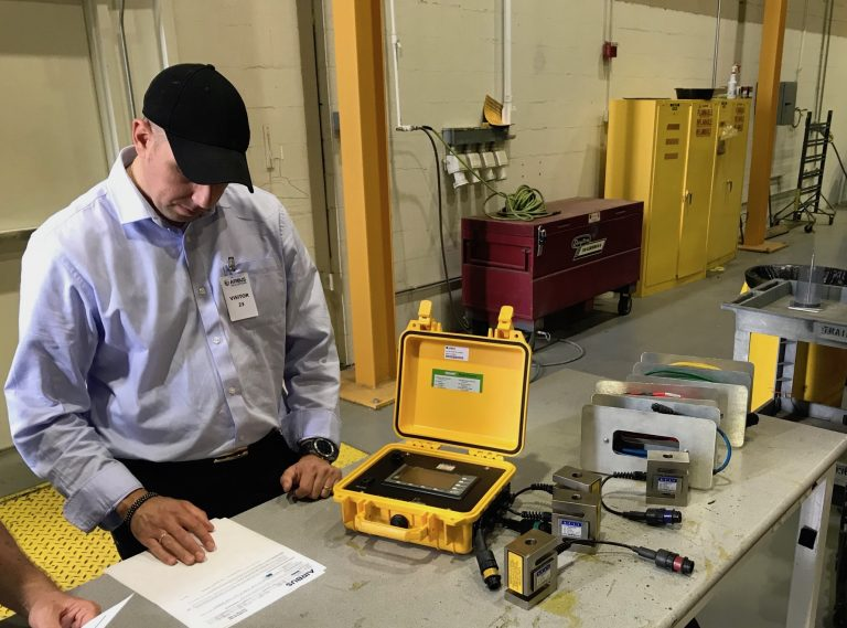 Technician looking at paperwork and preparing the helicopter weighing equipment, a yellow box with different coloured cables.