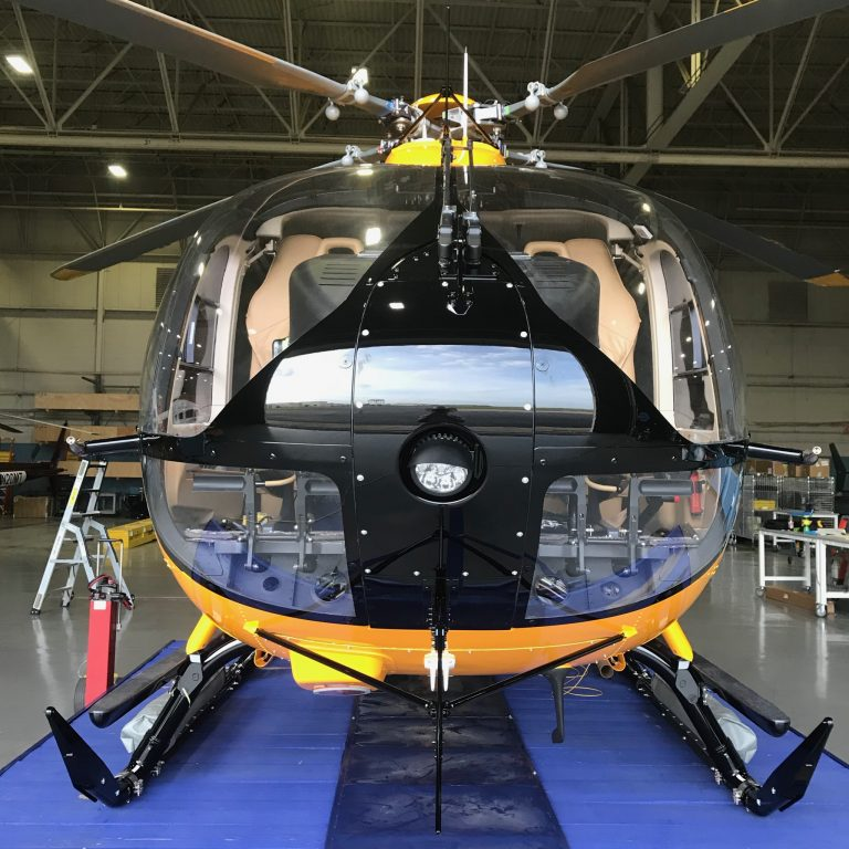 Yellow H145 Airbus Helicopter from the front on a blue mat in a hangar.